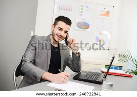 young man in office working with laptop computer and phone - stock photo