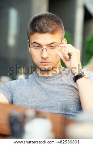 Young man in outdoor restaurant looking at the menu