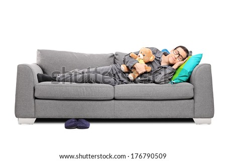 Young man in pajamas sleeping on couch with teddy bear isolated on white background - stock photo