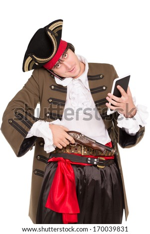 Young man in pirate costume posing with a tablet, mobile phone and pistol. Isolated on white