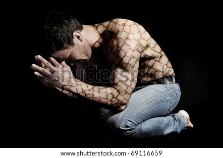 Young man in pose. Conceptual photo. Man in jeans with a strange unique artistic tattoo like rocks sitting in dark with hands on face. - stock photo