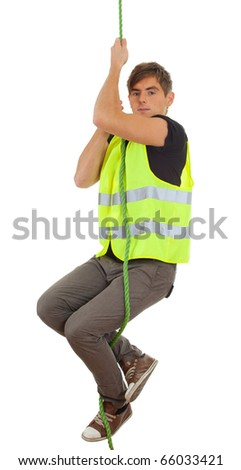 young man in protective waistcoat climbing on rope - stock photo