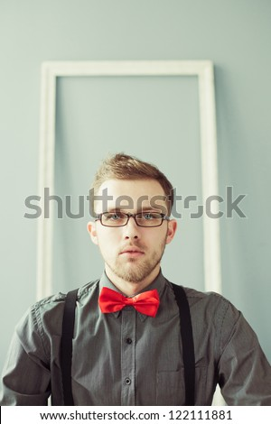 Young man in red bowtie and suspenders looking straight at camera - stock photo