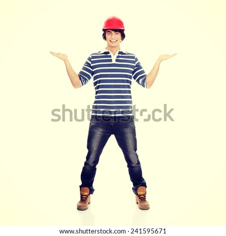Young man in red helmet presenting something on his hands - stock photo