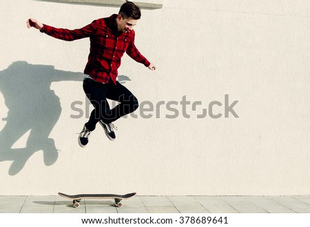 Young man in red shirt jumping on skateboard