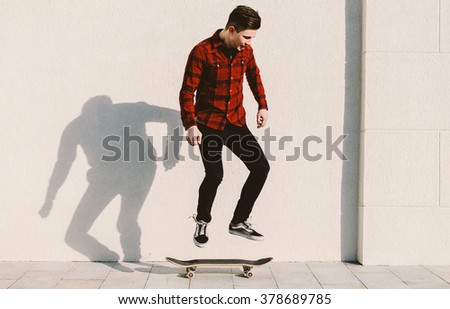 Young man in red shirt jumping on the skateboard - stock photo
