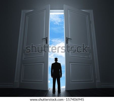 young man in room with big door to sky - stock photo