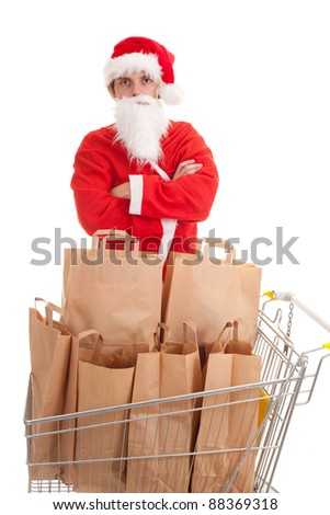 young man in Santa clothes with paper bags in shopping basket