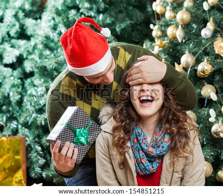 Young man in Santa hat covering woman's eyes while surprising her with gift at Christmas store - stock photo