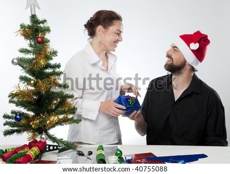 Young man in Santa hat giving his partner a gift. - stock photo
