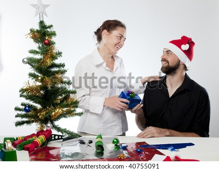 Young man in Santa hat giving young woman a gift.