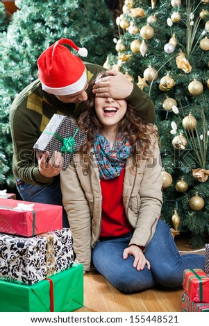 Young man in Santa hat surprising woman with Christmas gifts in store - stock photo