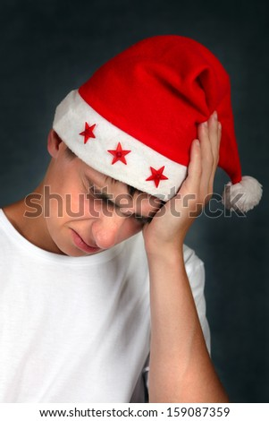 Young Man in Santa's Hat feels headache after Party - stock photo