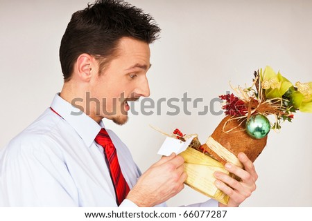 Young man in shirt and red tie hold Christmas gift and he is surprised - stock photo