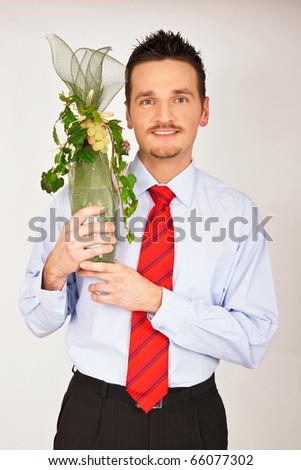 Young man in shirt and tie hold and shows gift. - stock photo
