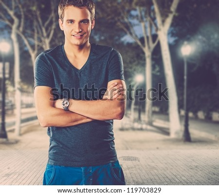Young man in shirt outdoors at night - stock photo
