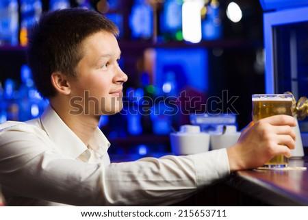 Young man in shirt sitting at bar - stock photo
