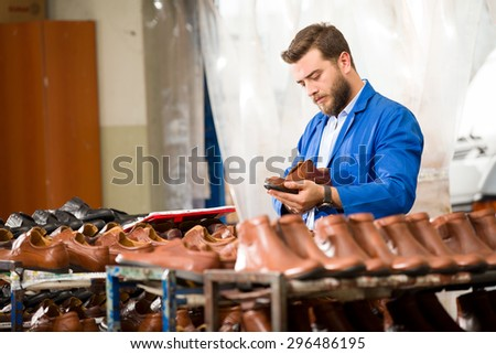 Young man in shoes factory. - stock photo