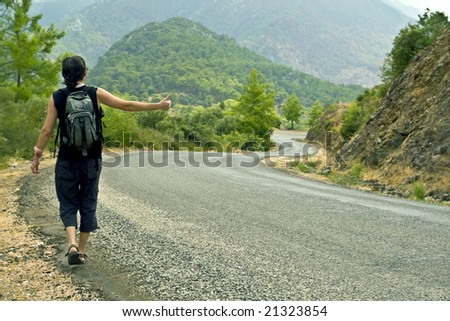 Young man in shorts and with backpack walks along the mountain serpentine road and thumbs a lift - stock photo