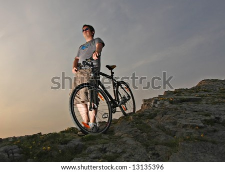 Young Man in Shorts with Hybrid Mountain bike on a rocky hill - Sunset with edgy lighting - stock photo
