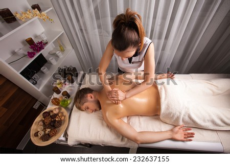 young man in spa salon which makes massage - stock photo