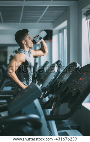 Young man in sportswear running on treadmill and drinking water at gym  - stock photo