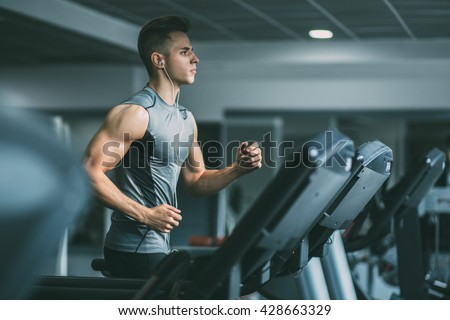 Young man in sportswear running on treadmill at gym - stock photo