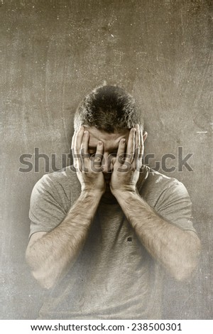 young man in stress suffering depression, headache , migraine , mental  breakdown and pain on grunge studio background covering face with hands in crisis - stock photo