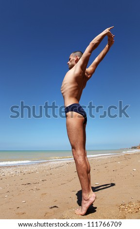 Young man in strong stretching yoga pose at the lonely beach - stock photo