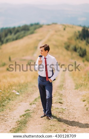 Young man in stylish suit standing on road at summer field with his blazer over shoulder - stock photo