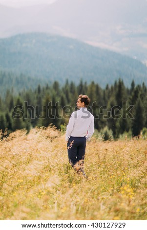 Young man in stylish suit standing on summer field. Forest hills at background - stock photo