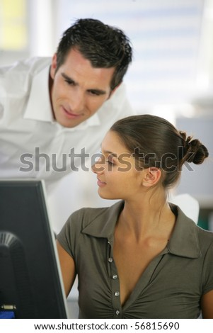 Young man in suit and young woman in front of a desktop computer