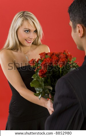 Young man in suit is giving flowers to beautiful, smiling woman. The man is standing back