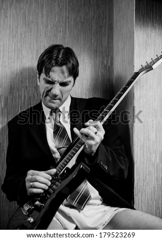 young man in suit playing rock guitar