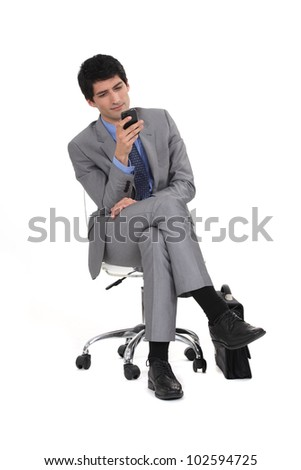 Young man in suit sending text message - stock photo