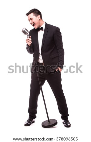 Young man in suit singing over the microphone with energy. Isolated on white background. Singer concept. - stock photo