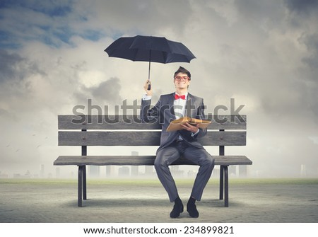 Young man in suit sitting on bench with book in hands