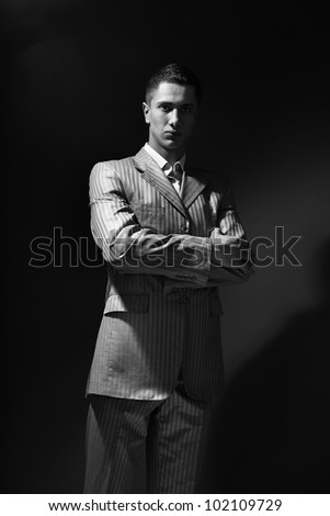Young man in suit standing in darkness - stock photo