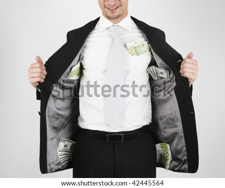 young man in suit that carry money (100s of dollar and euro) in his pockets. - stock photo
