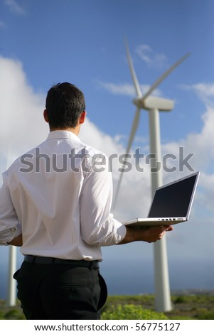 Young man in suit with a laptop computer face to a wind turbine