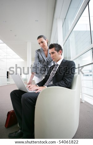 Young man in suit with a laptop computer next to a young woman - stock photo