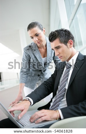 Young man in suit with a laptop computer next to a young woman