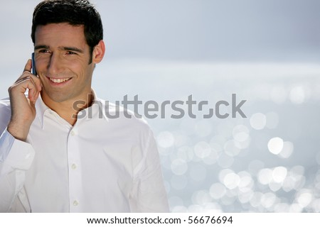 Young man in suit with a phone near the sea - stock photo