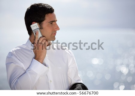Young man in suit with a phone near the sea