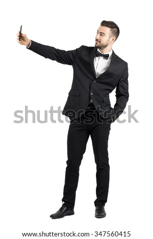 Young man in suit with bow tie taking selfie with cellphone. Full body length portrait isolated over white studio background.  - stock photo