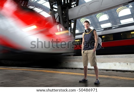 Young man in summer clothes standing on the platform of a train station - stock photo
