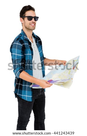 Young man in sunglasses holding map on white background