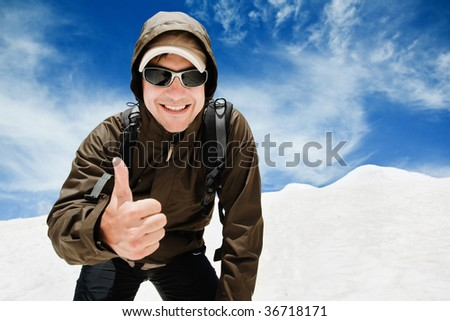 Young man in sunglasses is standing against blue sky