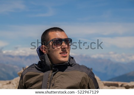 Young man in sunglasses is standing against blue sky in the top of the mountain