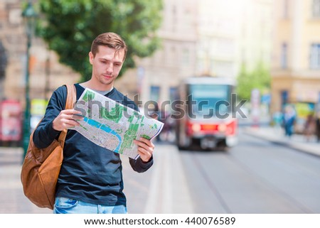Young man in sunglasses with a city map and backpack in Europe. Caucasian tourist looking at the map of European city in search of attractions. - stock photo
